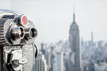 Image of coin operated binoculars overlooking the city in the background